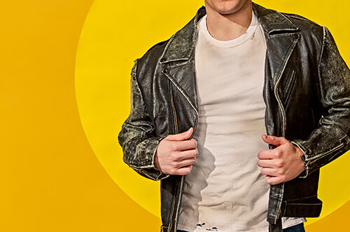 A young man with a leather jacket and white teacher is centered in the frame with a bright yellow background